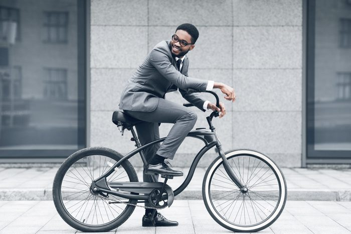 Keep calm and ride on. Businessman cycling against office buiding, going to work