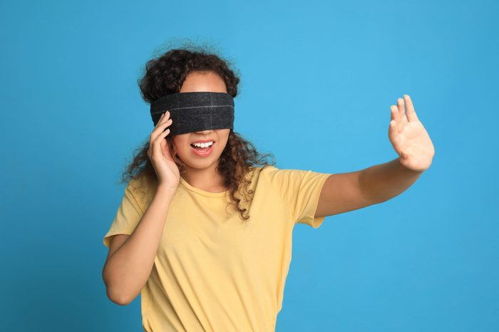 Young African-American woman with black blindfold on blue background