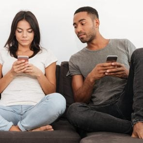 Photo of young couple using their cellphones sitting on sofa at home. Boy looking at woman's phone.