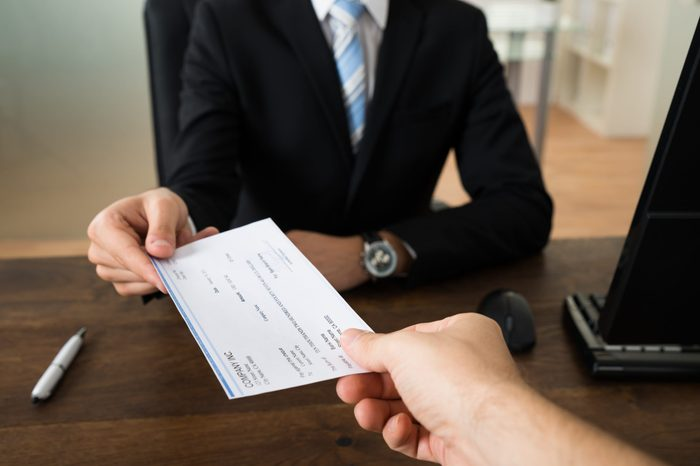 Close-up Of Businessman Hands Giving Cheque To Other Person In Office