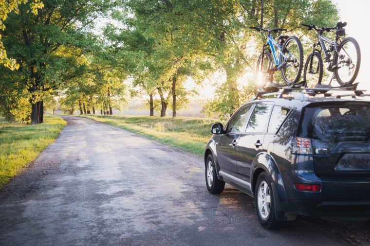 Car with bicycles in the forest road at sunset