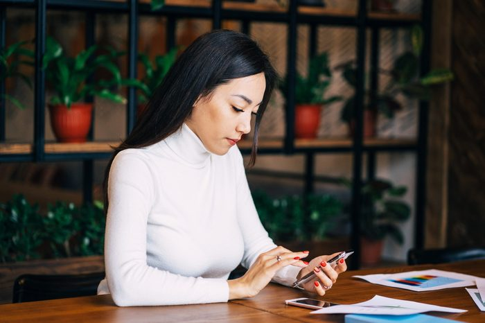 Positive kazakh businesswoman is thinking about tomorrow working plans and sending email to her boss using phone in the public place. Beautiful young female is doing her work in the cafe.