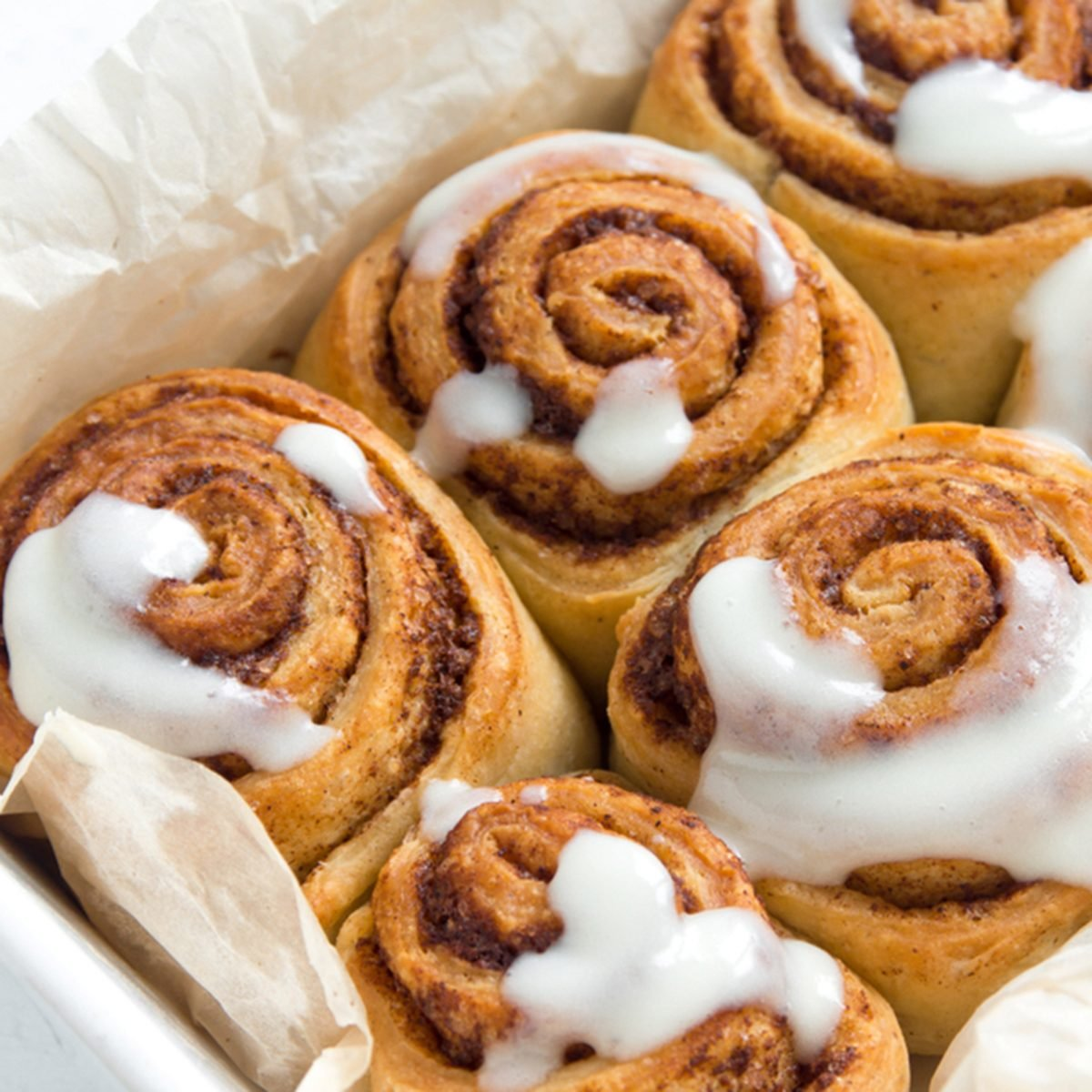 Cinnamon rolls or cinnabons with cream sauce, homemade recipe preparation sweet traditional dessert buns pastry food close up.