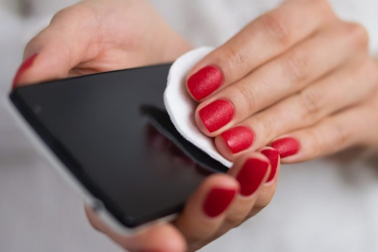 Care and clean the phone with a cotton pad. Female hands holding a mobile phone and wipe the screen cloth.
