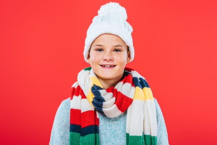 front view of smiling kid in hat and scarf isolated on red