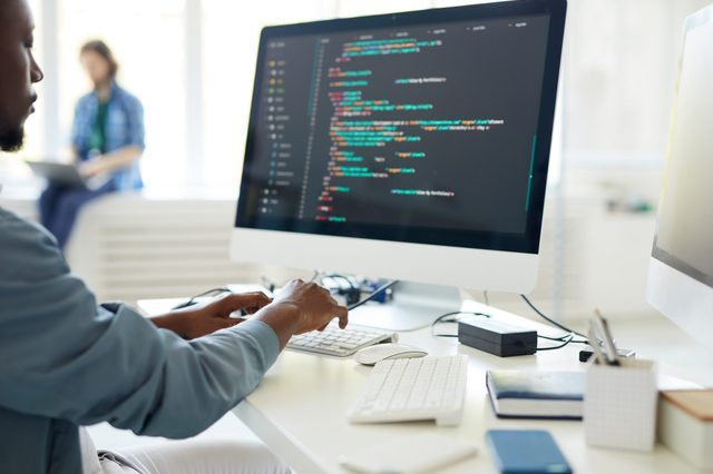 Computer programming specialist working on desktop computer and composing web code while carrying out task from order in office