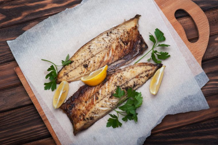 Grilled fish with herbs and lemon on rustic dark wooden background
