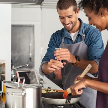 Young man cooking with girlfriend and adding spice to the sauce. Guy adds black pepper into frying pan on stove while woman using spatula to mix. Multiethnic couple preparing lunch together at home.