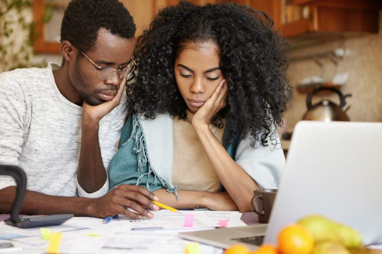 Sad African family facing financial difficulties, having many debts, calculating domestic expenses, forced to save money on groceries to pay off their loan, sitting in kitchen with laptop and papers