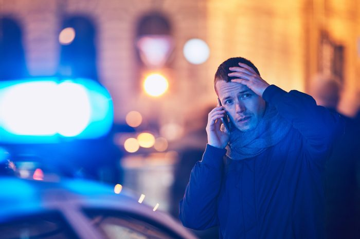 Young man calling after a crisis situation on city street. Themes crime, emergency medical service, fear or help.