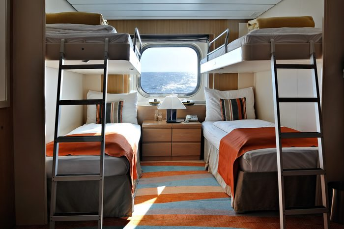 interior of a living cabin on a cruise ship - with bunk beds and window
