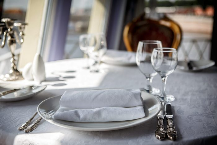 Served table on the ship. Serving of the dinner table in the cabin restaurant ocean liner. Food and service at the marine ship. Utensils for passenger cruises.