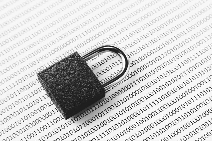 a black and white concept image that can be used to represent cyber security or the protection of software code. This image has selective focusing on the padlock