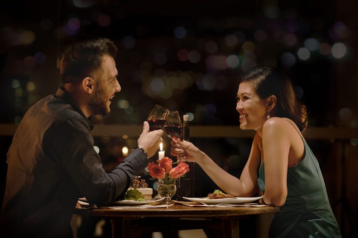 Cheerful couple clinking glasses at late romantic date in restaurant