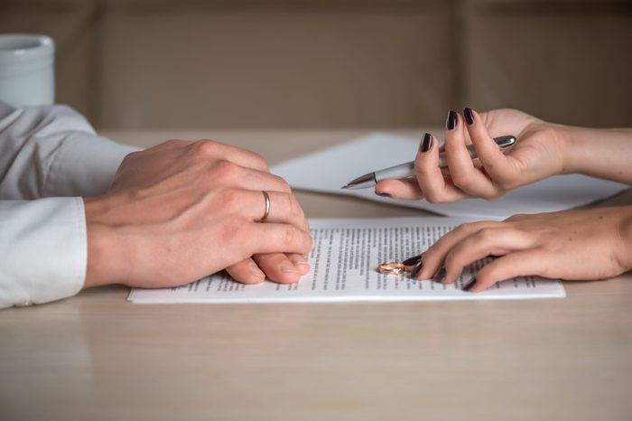 Wife and husband signing divorce (dissolution of marriage) documents, filing divorce papers prepared by lawyer, canceling marriage, performing legal or de jure separation, woman returning wedding ring