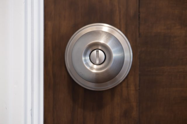 closeup, straight on, front view of a silver stainless steel doorknob on a brown wooden entry door to a room