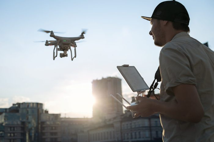 Man with drone flying at the city