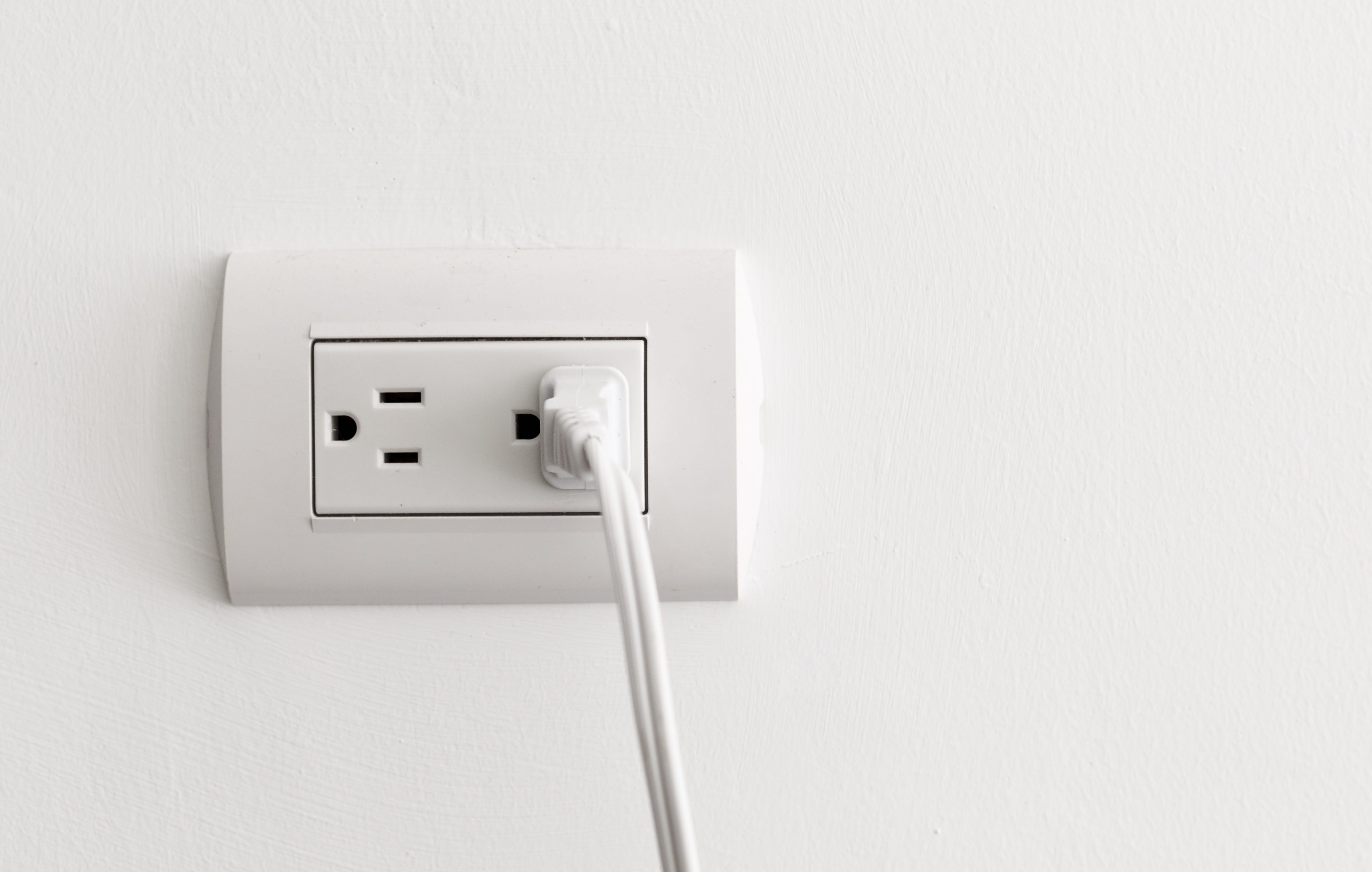American electrical socket on white wall, copy space