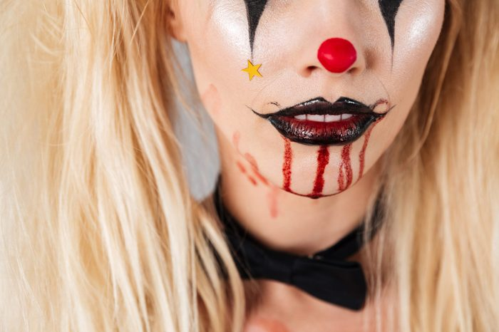 Cropped image of a blonde female face in halloween make-up isolated over gray background