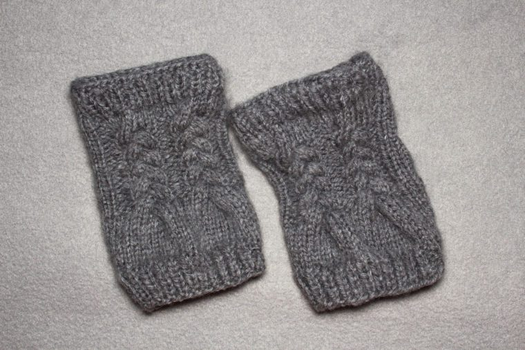 knitting women's gloves mittens without fingers from gray wool yarn, auxiliary needle, braided pattern