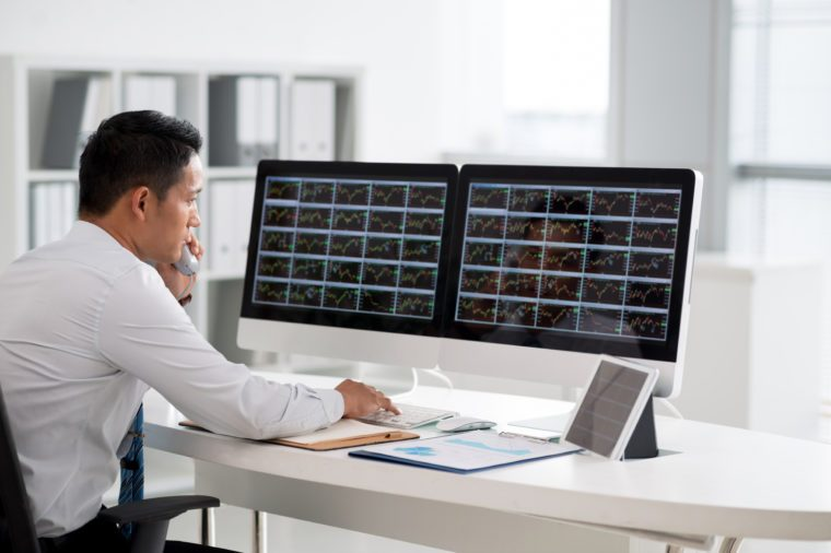 Financial analyst looking at the monitors and talking on phone