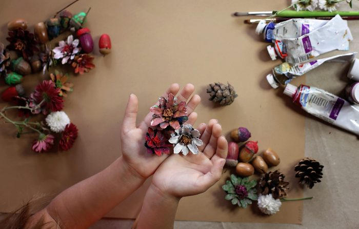 Little kid hands coloring a natural cone fir to create a flower for thanksgiving