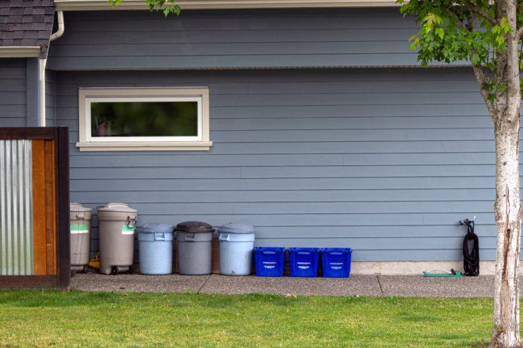 street scene, garbage cans and recycling tubs at side of blue house