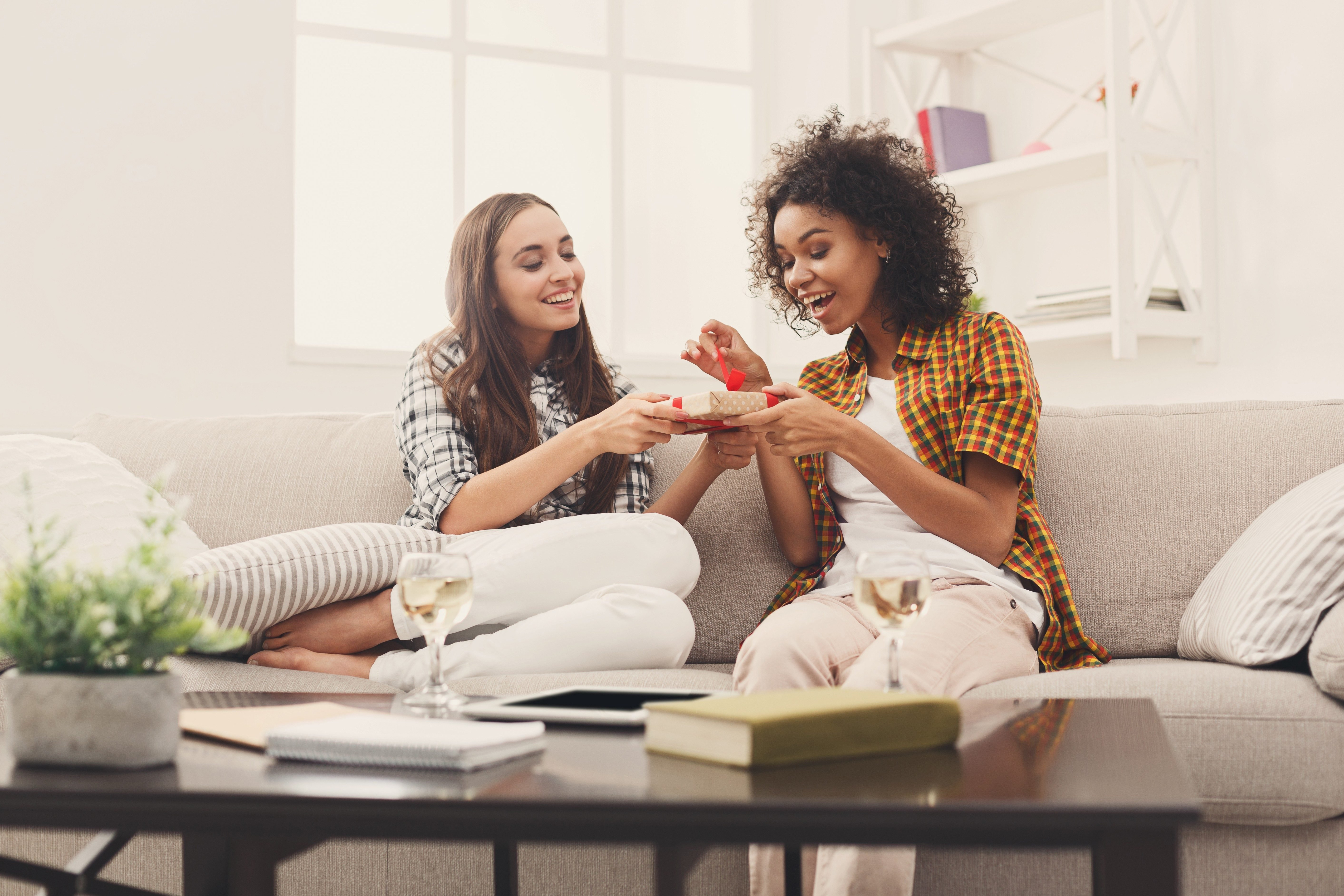 Happy girls exchanging gifts. Excited woman getting present from her friend. Birthday, holidays, celebration and female friendship concept, copy space