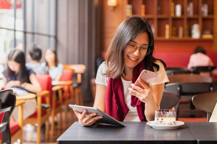 Lifestyle, Technology Concept - Asian woman using app on a smart phone while relaxing in cafe during free time with copy space.