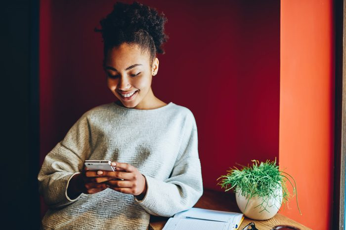 Cheerful dark skinned female blogger checking email and send text message via smartphone on free time, smiling dark skinned hipster girl reading news and updates in social networks using mobile phone