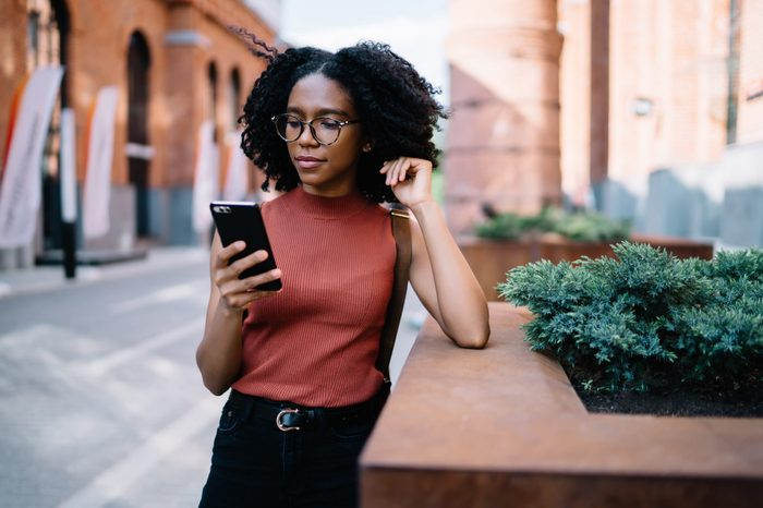 Millennial hipster girl in checking email box notifications on smartphone application while standing outdoors . female buying tickets in baking application, attractive young woman using mobile phone