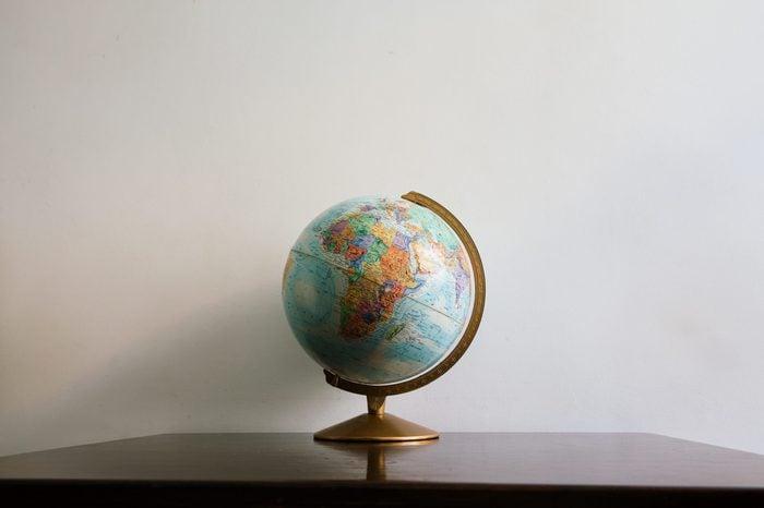 Globe model on dark wooden desk. White wall empty space background.