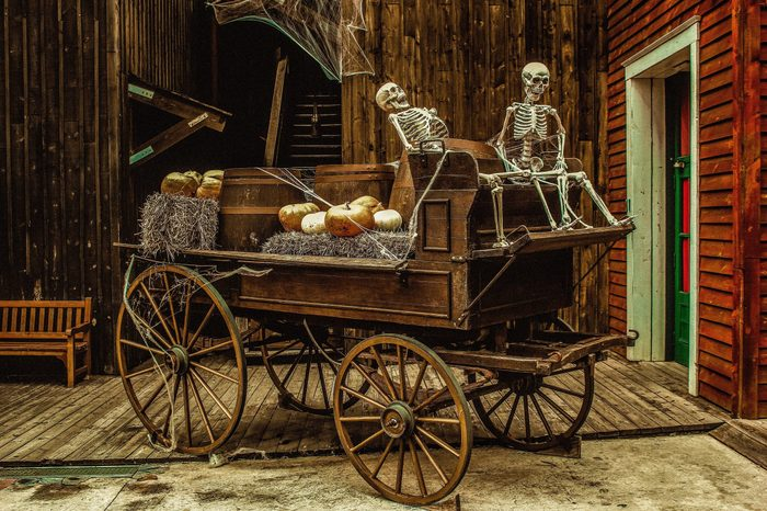 An old carriage with two skeletons, decorated with pumpkins, barrels, hay and cobwebs. Halloween decoration.