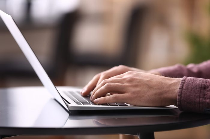 Young man working with laptop at home, closeup