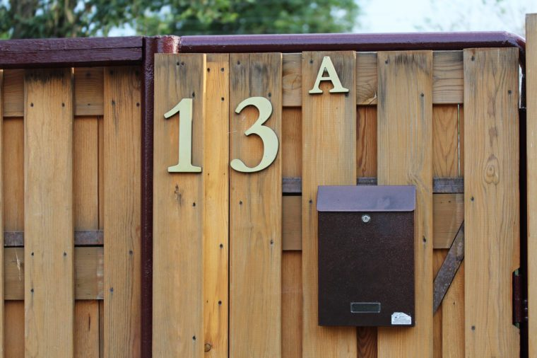 House number 13A on a wooden fence with a mailbox