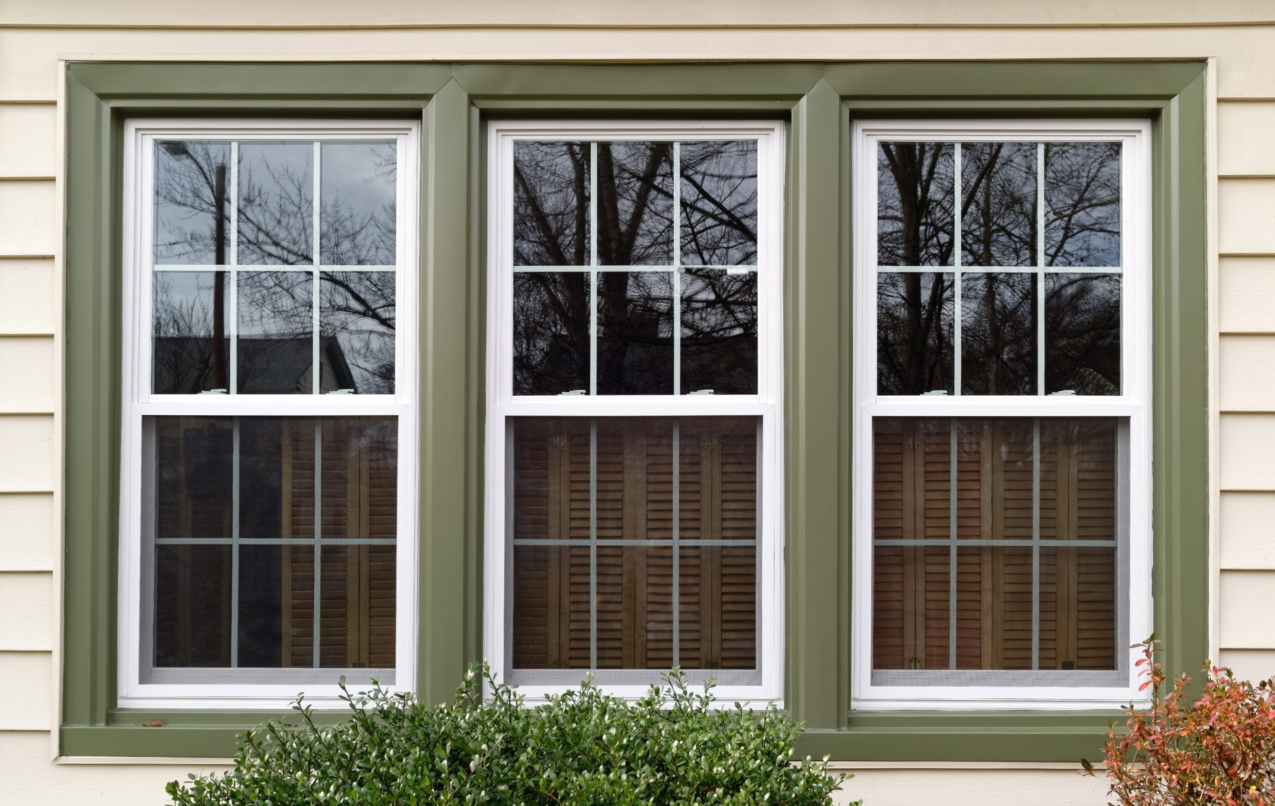 Three new replacement windows with green trim on front of house. Horizontal.