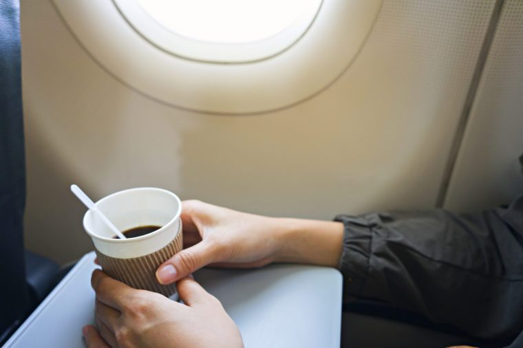 Tourists holding a cup of white coffee on the plane.A cup of coffee on the foldable tray of the aircraft seat.