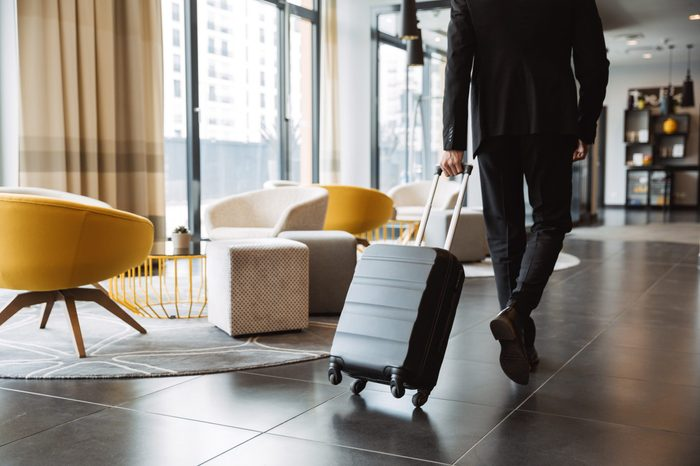 Cropped photo of caucasian businessman wearing formal black suit walking with suitcase in hotel lobby
