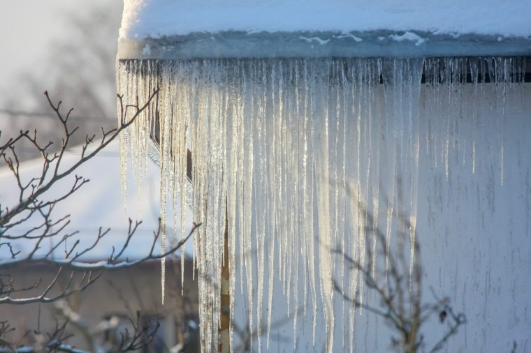 The roof of a house covered with snow and icicles. Icicles hanging from roof. Winter in Latvia. White snow on the roof and icicles hanging from a slate roof.