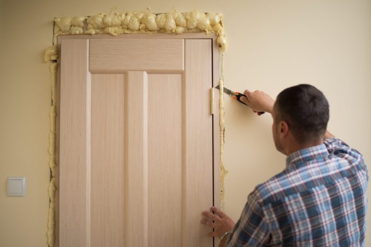 Ð¡utting foam after mounting a door. Handyman knife cuts off excess mounting foam. Installation of doors using polyurethane foam mounting. Polyurethane foam for thermal insulation.
