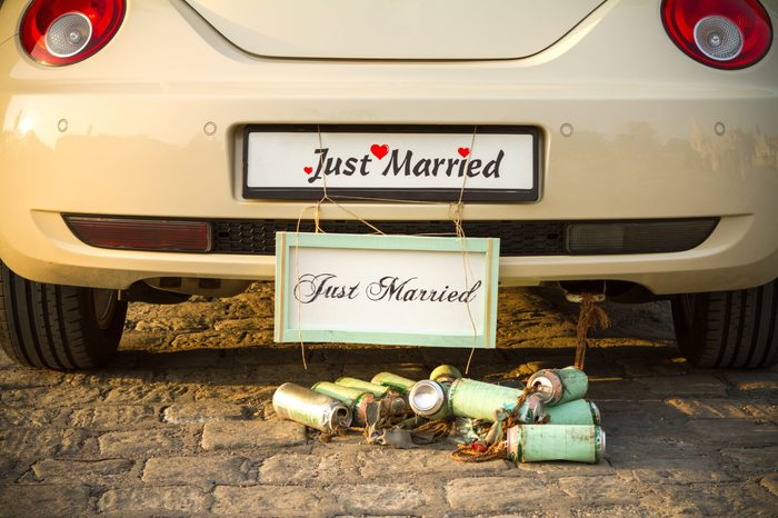 """Wedding car with a plate """"Just married"""" and a bunch of a beer cans."""
