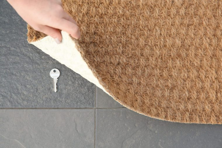 Young woman revealing hidden key under door mat, top view with space for text