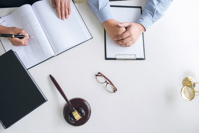 Close up of gavel, Male lawyer or judge Consult with client and working with Law books, report the case on table in modern office, Law and justice concept. Top view.