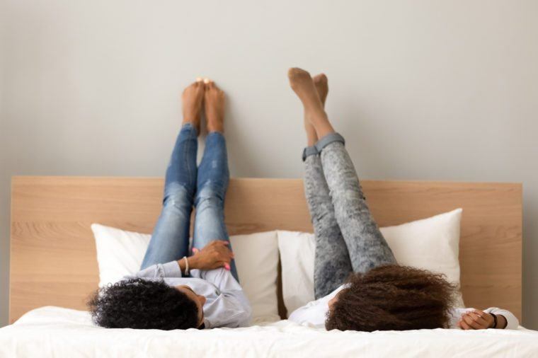 African girls gossiping best friends lying on bed raised their legs up. Girlfriends or sisters chatting talking secrets dreaming together spending time on lazy weekend at home or hotel during holidays
