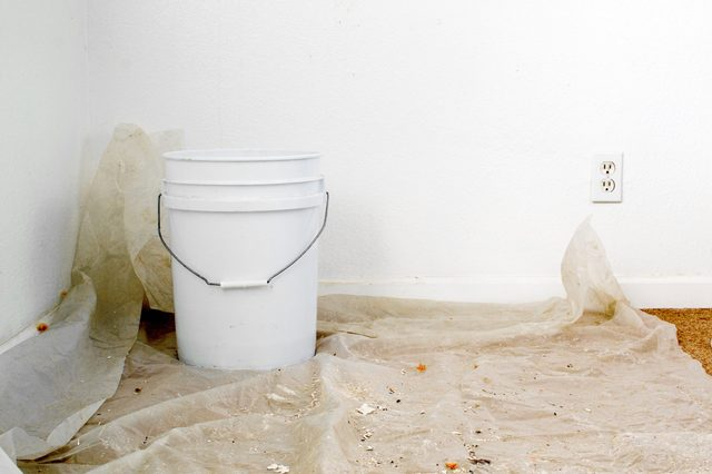 A white bucket over a sheet of plastic placed over carpet floor to collect water from leaking ceiling