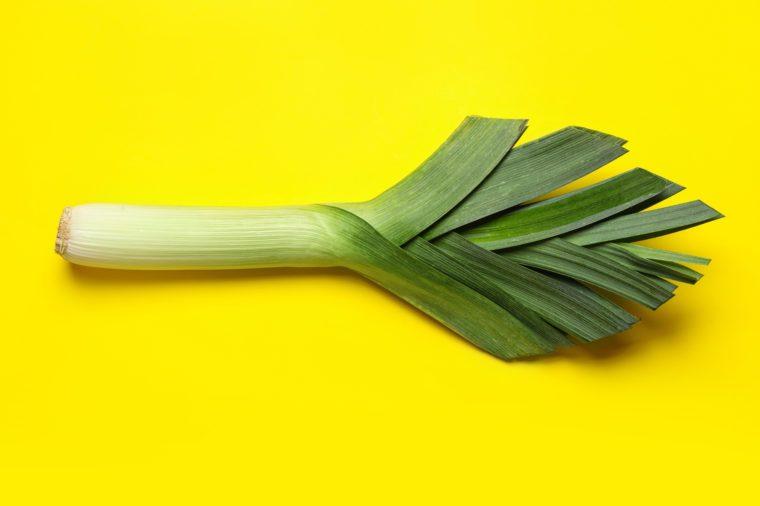 Fresh raw leek on yellow background, top view. Ripe onion