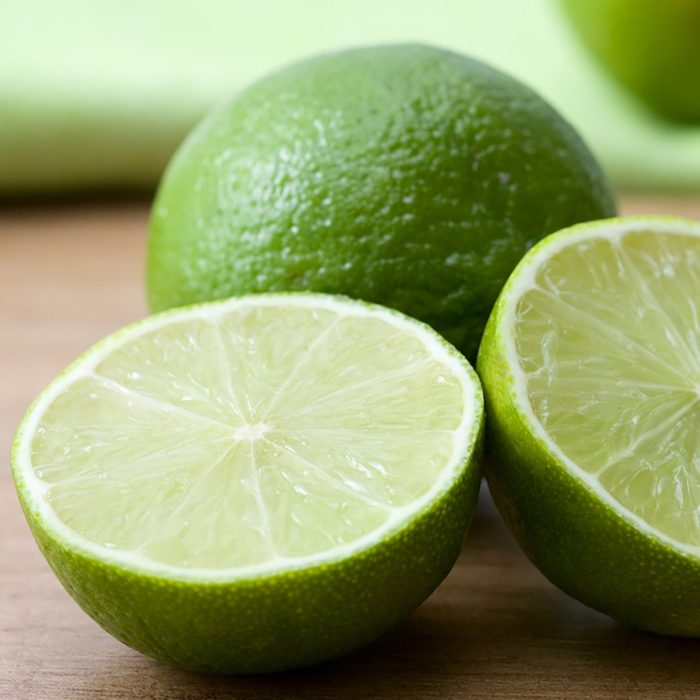 Close-up of cut green limes on a wooden background.