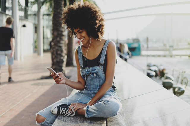 beautiful mixed race girl with afro hair listening to her favorite music through headphones using a mobile phone. an attractive black young woman adds a new track to her playlist using a mobile app