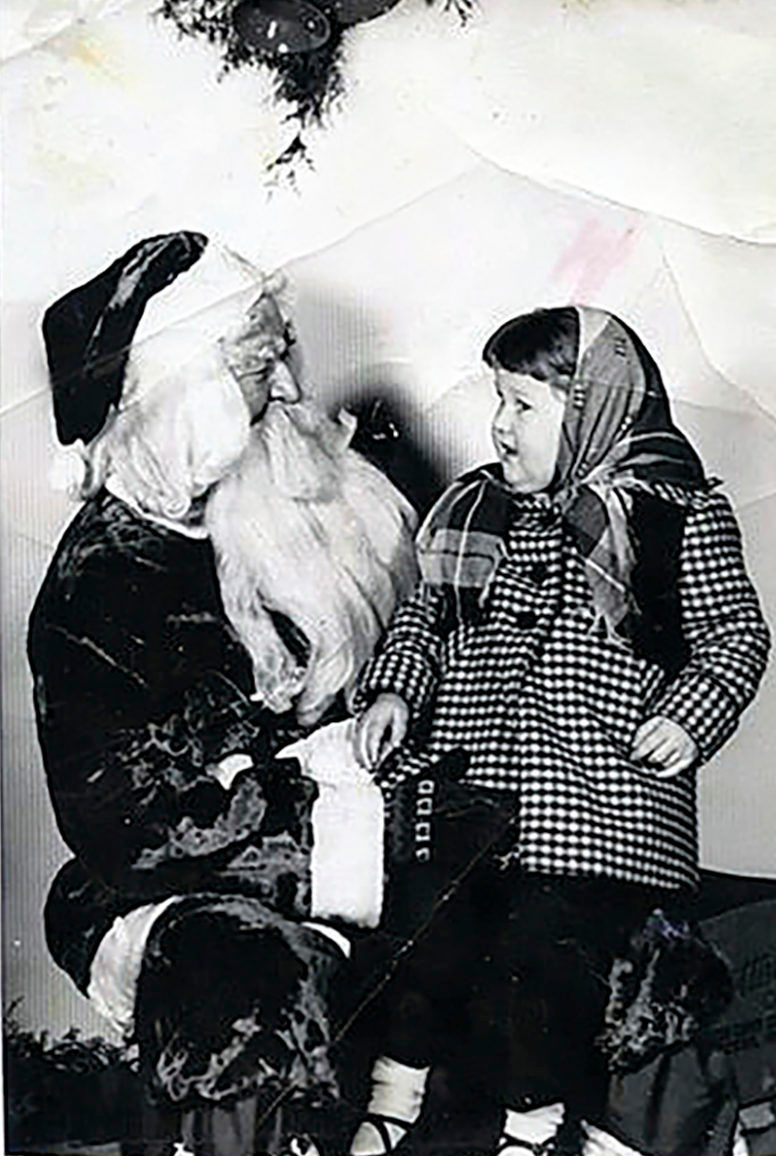 little girl sitting on santa's lap - plaid coat
