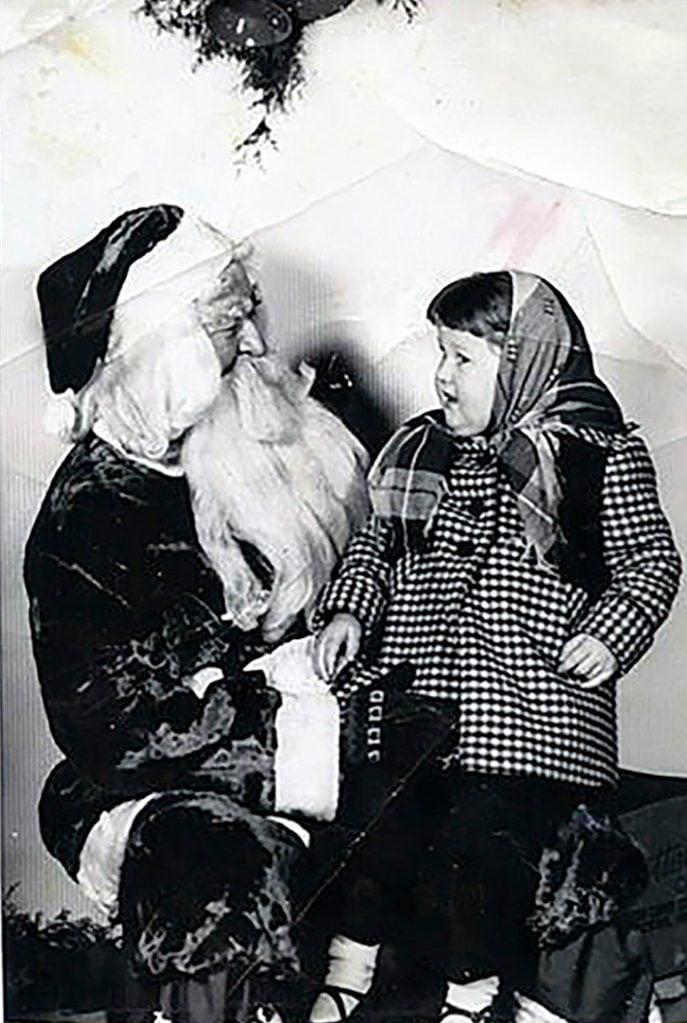 little girl sitting on santa's lap - plaid coat